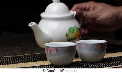 Pouring tea to teacups