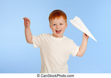 Adorable red-haired boy with paper plane model on blue background in studio