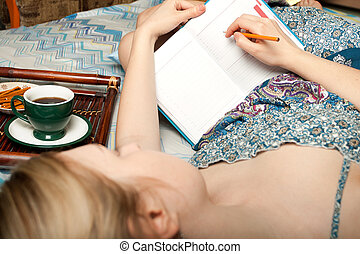 girl with cup of coffee writing something - dreaming girl...