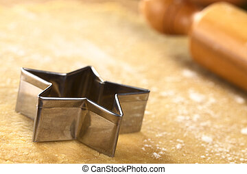 Star-shaped cookie cutter on dough
