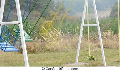 Swinging empty colored swings