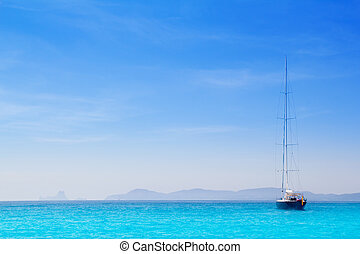 Ibiza mountains with sailboat from Formentera turquoise sea