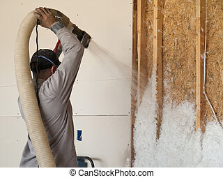 Fiberglass Insulation Blower - Worker blowing fiberglss...