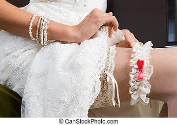 White garter, dressed on the Bride?s leg.