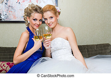 The bride and her bridesmaid with a glass of wine on the...