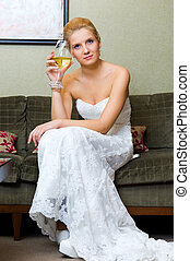 The bride with a glass of wine in a beautiful interior