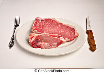 Raw T-Bone Steak - A raw t-bone steak is laying on a white...