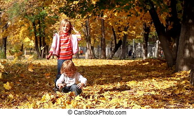 Yellow game - Children playing with leaves in autumn park