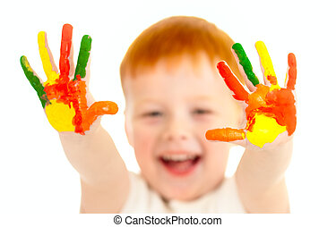 Adorable red-haired boy with focus on hands painted in bright colors