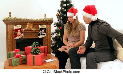 Gifts for the New Year - Young couple give each other gifts...