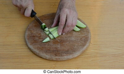 pensioner hands cut up cucumber