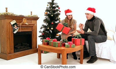 Christmas spirit - Young girl and man sign gifts to avoid...
