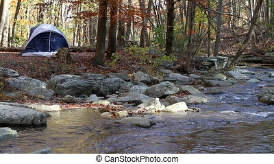 Camping By Mountain Stream - Small camping tent is pitched...