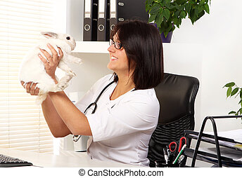Woman veterinarian is checking health of white rabbit