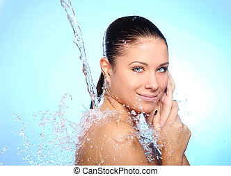 Beautiful woman under splash of water against blue...