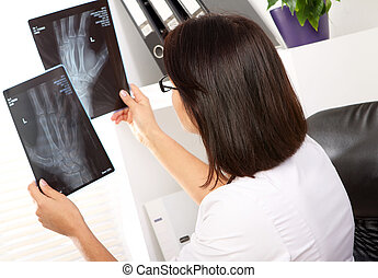 Woman doctor is looking at xray of broken hand - Young woman...