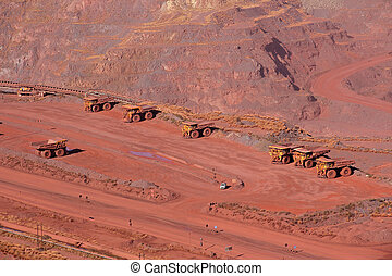 Iron ore mining - Large, open-pit iron ore mine with trucks...