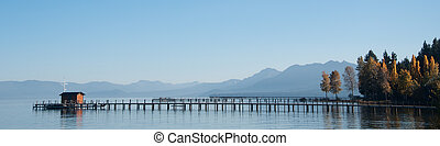 Lake Tahoe - Rocky shore and mountain background at blue...