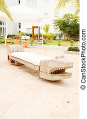 Home exterior patio with handcraft wooden sofa with an aligator appearance.