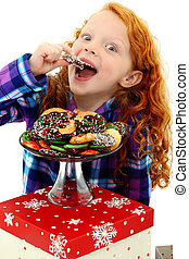 Beautiful Excited Girl Child in Pajamas with a Tray of Holiday Cookies over white background.