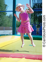The little girl  on a trampoline in park
