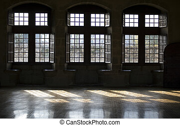 Three French windows with braces and reflection on floor in...