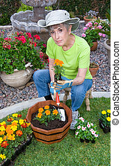 Adult planting flowers - A senior adult relaxes in her...