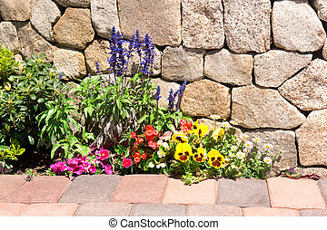 Flower garden along stone wall - A garden next to a stone...