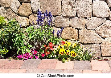 Flower garden along stone wall - A garden next to a stone...