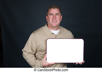 Businessman holding blank whiteboard - A businessman dresses...