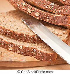 Brown bread - Sliced wholemeal bread and a bread knife on a...