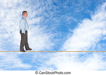 Businessman walking on tightrope - A businessman walks...