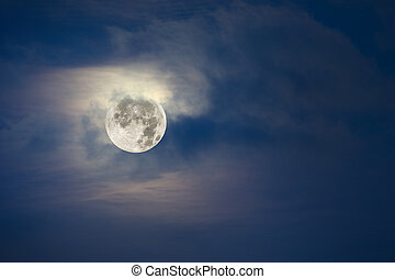 Full moon and cloudy sky - A brightly lit full moon lights...