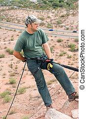 Rock climber rappelling - A rock climber begins to rappel...
