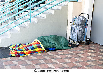 Homeless person sleeping - A homeless person sleeping along...