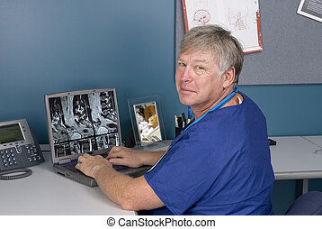 Doctor reviewing MRI on laptop - A doctor reviews an MRI on...