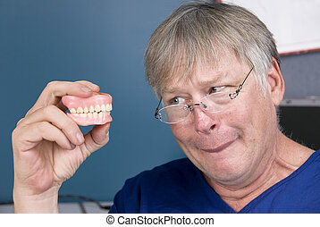 Man and his dentures - A man stares at his dentures before...