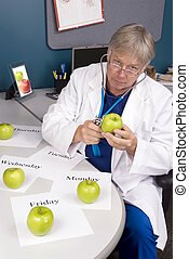 Doctor examines an apple - A doctor examines an apple with...