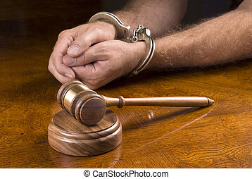 Arrested man and gavel - A man arrested awaits the judge to...