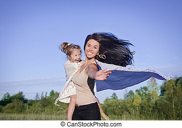 happines - a mum and daughter having fun in the fields