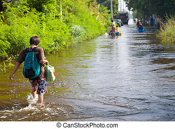 Thailand flood - People wading through the streets of the...