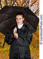 woman in rain coat with umbrella walking at autumn forest