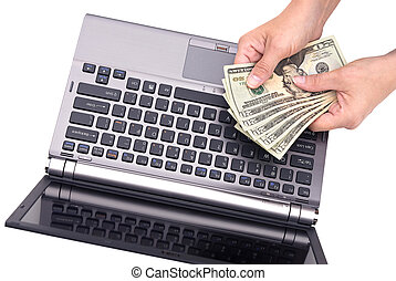 Counting cash on laptop - A woman counts her cash while...