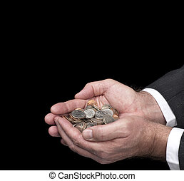 Man holding coins - A man cups his hands as he holds a pile...