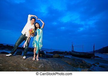 young couples making heart sign at the beach