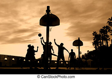 Basketball players at sunset play hard for the winning shot