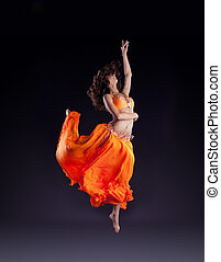 beauty dancer jump in orange veil - arabian style