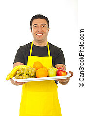 Happy fruiterer offering fresh fruits isolated on white...