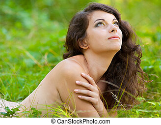 Woman lying naked in grass - Portrait of a woman lying naked...