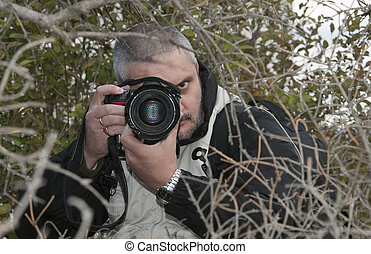 Photographer hidden - Photographer hidden behind a dense...